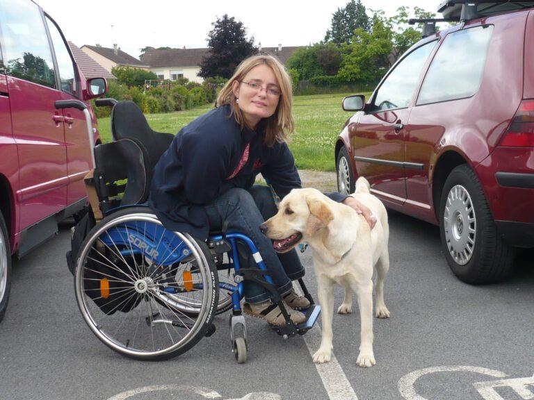 Das Photo zeigt eine Frau im Rollstuhl die lächelt und einen hellen Labrador streichelt